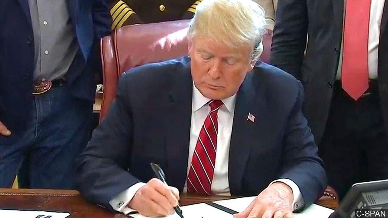 Trump signs VETO, 3-15-2019_1552689278907.jpg.jpg