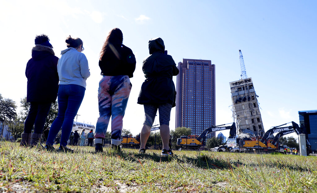 "People gather to watch the demolition of the so called ""Leaning Tower of Dallas"" as a wrecking ball works to topple the structure north of downtown Dallas, Monday, Feb. 24, 2020.  (AP Photo/LM Otero)"